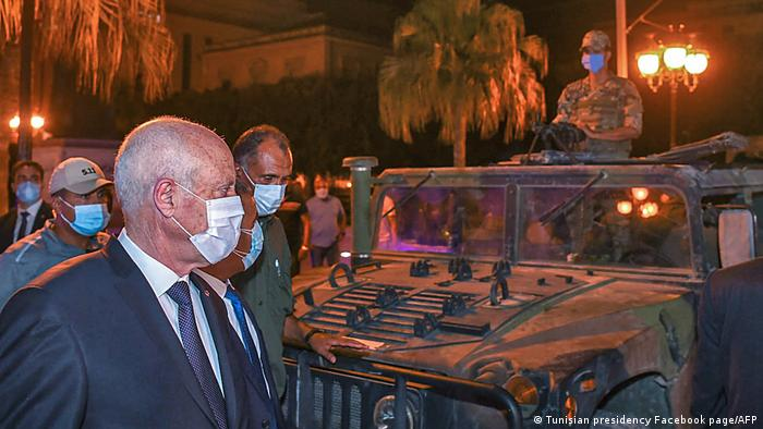 President Kais Saied, wearing a face mask, and other men walk past a jeep at night