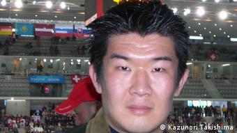 Cabeça de homem japonês, com arquibancadas de ginásio ao fundo