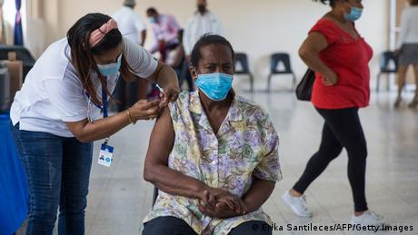 A nurse administers a vaccination to a woman in the Dominican Republic