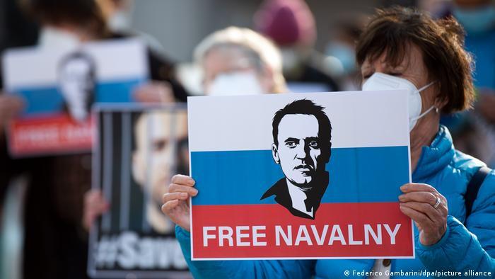 Frau hält ein Plakat mit Nawalnys Konterfei und dem Slogan Free Navalny (Dt. Lasst Nawalny frei)