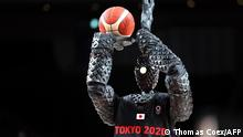 A basketball-playing robot named CUE plays basketball during half-time of the Men's Preliminary Round Group B game between the United States and France on July 25, 2021, during Tokyo 2020 Olympic Games at Saitama Super Arena. - Toyota has created a 6-foot-10-inch basketball-shooting robot named Cue that uses sensors on its torso to judge the distance and angle of the basket and uses motorized arms and knees to execute set shots. (Photo by Thomas COEX / AFP)