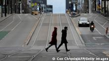 Pedestrians walk through the quiet streets of Melbourne