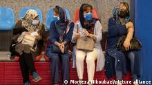 Iranian women wearing protective face masks sit together after receiving a dose of China's Sinopharm new coronavirus disease (COVID-19) vaccine, at a sports hall in central Tehran on July 19, 2021. (Photo by Morteza Nikoubazl/NurPhoto)