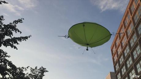 A green helium drone flies near a building