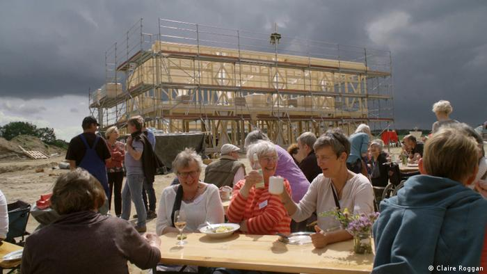 Film still Wir alle. Das Dorf , people siting at long tables outdoors, a building going up in the background
