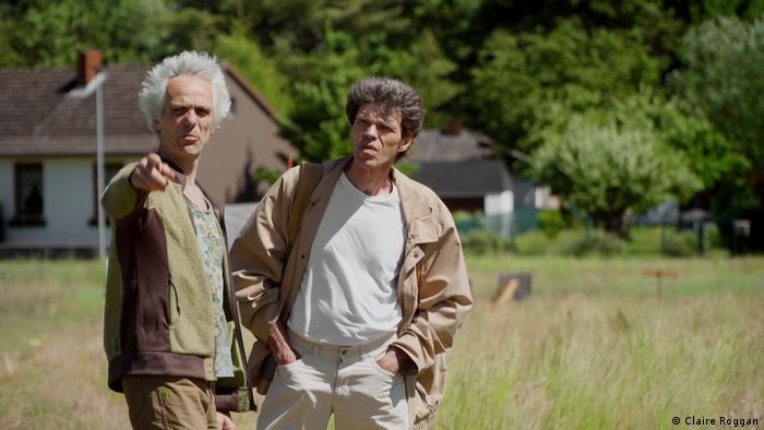 Film still Wir alle.  Das Dorf, two men in a field, houses in the background, one points to the camera