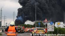 Einsatzfahrzeuge der Feuerwehr stehen unweit einer Zufahrt zum Chempark über dem eine dunkle Rauchwolke aufsteigt. Nach einer Explosion seien Feuerwehr, Rettungskräfte und Polizei aktuell im Großeinsatz, erklärte die Polizei. Wegen der Schadenslage ist die viel befahrende Autobahn A1 bei Leverkusen gesperrt worden. +++ dpa-Bildfunk +++