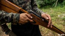 This photo taken on July 7, 2021 shows a member of the Karenni People Defense Force (KPDF) holding a homemade gun adorned with the words Spring Revolution in Myanmar script as he takes part in training at a camp near Demoso in Kayah state. - In their camp hidden in the forested hills of Kayah state near the Thai border, Myanmar anti-junta volunteers practice firing their homemade weapons, do physical training, and play guitar in between skirmishes with the military. (Photo by STR / AFP) / To go with 'MYANMAR-POLITICS-MILITARY-COUP,PHOTOESSAY'