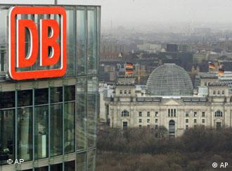 The logo of Deutsche Bahn is seen on the building of the DB's headquarters in Berlin with the Reichstag building in the background
