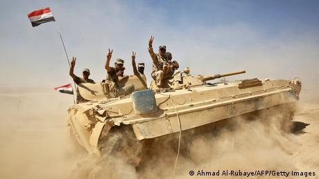 Iraqi soldiers wave from a tank in the desert.