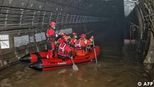 This photo taken on July 26, 2021 shows rescuers searching inside the subway which was flooded following heavy rains in Zhengzhou, in China's central Henan province. (Photo by STR / AFP) / China OUT