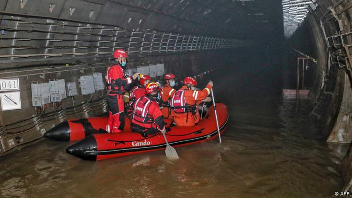 Rescuers search inside the subway which was flooded following heavy rains in Zhengzhou
