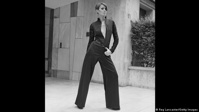 Woman with short hair modelling a low cut black jumpsuit.