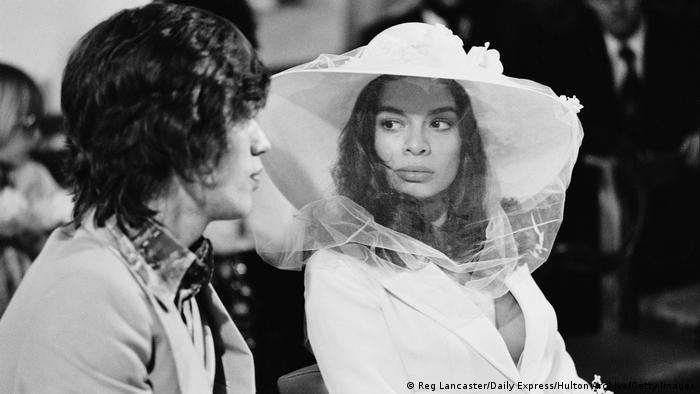 Man in a suit looking at a woman in a white tuxedo jacket with large veiled hat