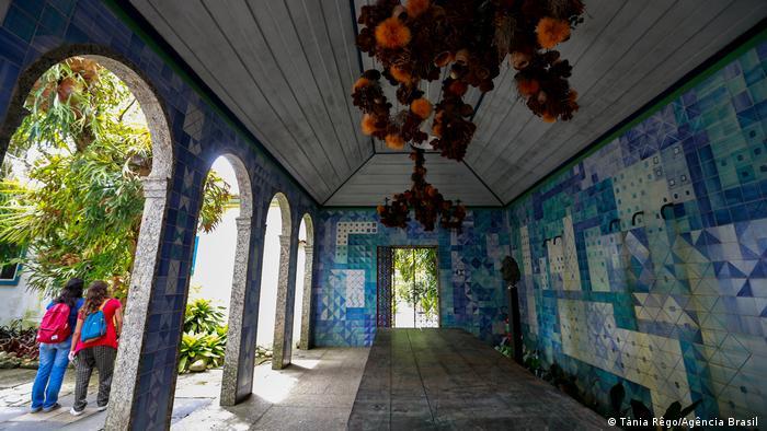 Foto mostra prédio, com arcos. As paredes parecem ser cobertas por azulejos de várias tonalidades de verde e azul.