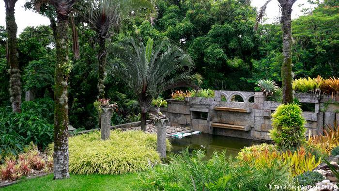 Foto mostra jardim no Sítio Roberto Burle Marx com uma fonte. Há muitos tons de verde.