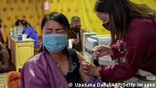A health worker inoculates woman with the jab of the Covid-19 coronavirus vaccine at a temporary vaccination centre in Thimpu on July 26, 2021. (Photo by Upasana DAHAL / AFP) (Photo by UPASANA DAHAL/AFP via Getty Images)
