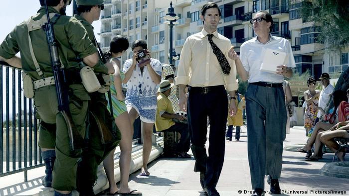 In einer Szene des Films München laufen zwei Männer über eine Promenade, umgeben von Touristen und Militär.