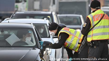 Policiais de máscara falam com um motorista dentro do carro