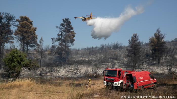A firefighting airplane drops water during a forest fire at Dionysos northern suburb of Athens