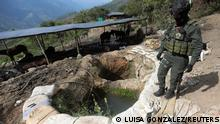 FILE PHOTO: A policeman stands next to a well where minerals taken from illegal gold mines are washed in Buritica, Colombia April 20, 2021. Picture taken April 20, 2021. REUTERS/Luisa Gonzalez/File Photo