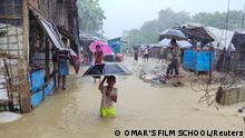 A boy plays in the flooded street after heavy monsoon rains triggered flooding at Kutapalong refugee camp, in Cox's Bazar, Bangladesh July 27, 2021 in this picture obtained from social media. OMAR'S FILM SCHOOL/via REUTERS THIS IMAGE HAS BEEN SUPPLIED BY A THIRD PARTY. MANDATORY CREDIT. NO RESALES. NO ARCHIVES.