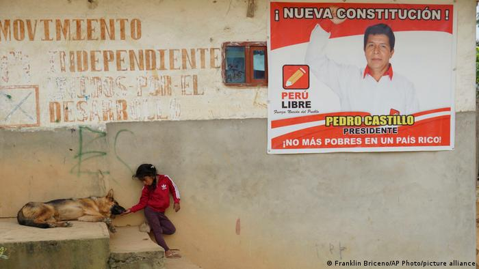 A small child is playing with a dog. On the wall next to them is a poster of Pedro Castillo that reads no more poor people in a rich country