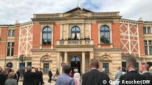 Besucher der Bayreuhter Festspiele hören die Fanfahren vor Beginn der Oper. 26.07.2021
