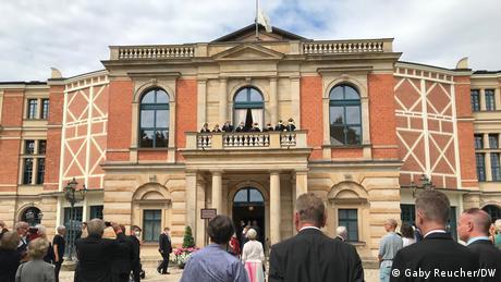 Besucherinnen und Besucher vor dem Bayreuther Festspielhaus schauen hoch zum Balkon.