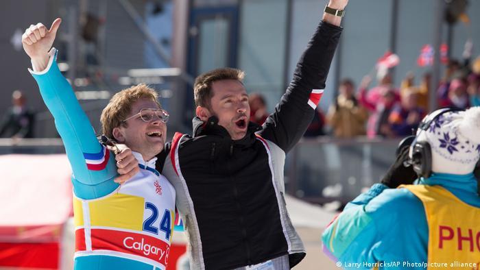 In einer Szene des Films Eddie the Eagle reißen ein Skispringer und sein Trainer jubelnd die Arme hoch.
