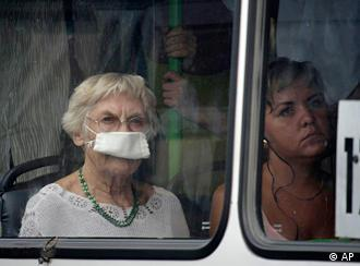 Riding in a bus a woman wears a mask protecting her from a thick blanket of smog covering Moscow