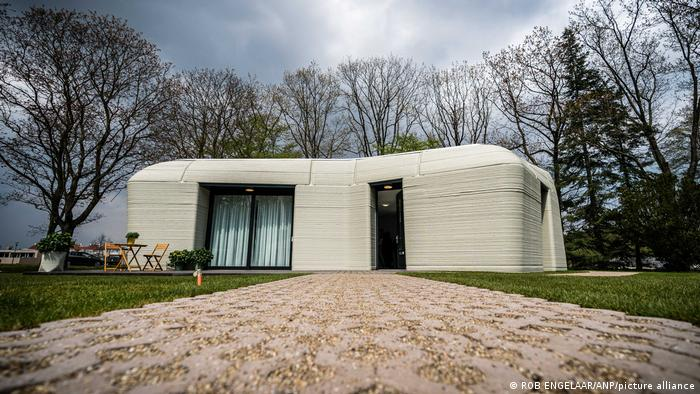 A 3D-printed home with large windows and a door, surrounded by a lawn and trees, built by Dutch architects together with the Eindhoven University of Technology