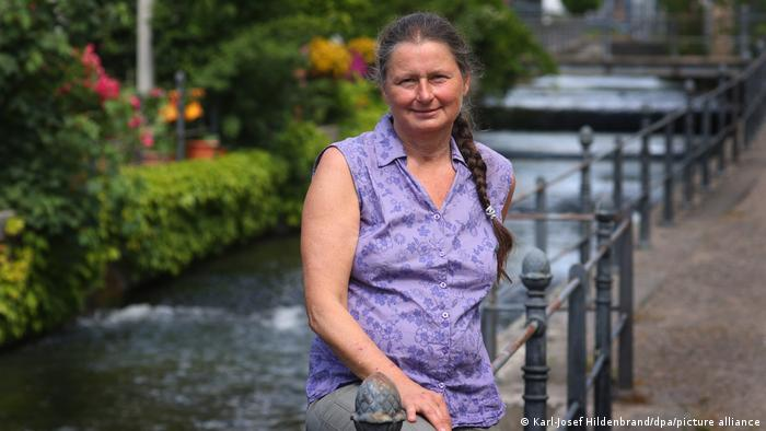 Christiane Renz sits on a fence next to the fishing stream