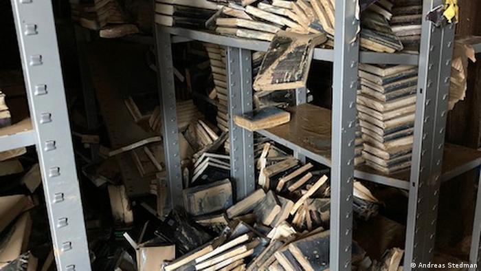 Bücher, die ungeordnet auf Metallregalen liegen