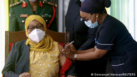 President Hassan sits in a chair while a nurse injects her in her arm