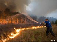 A fire fighter attempts to extinguish a forest fire
