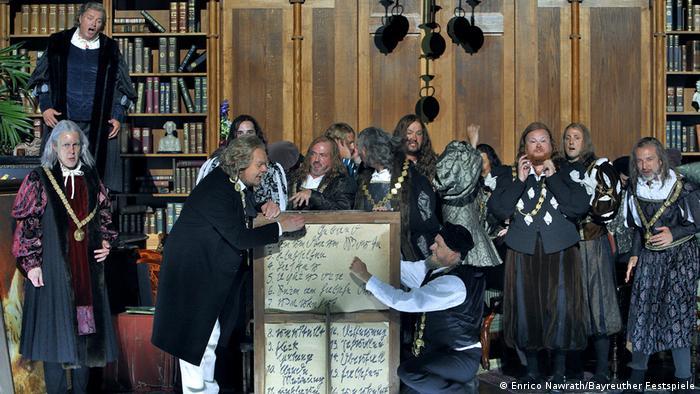 Männer haben sich um Wagner versammelt, der auf die Rückseite eines Bildes schreibt.