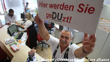 Sigbert Prestel, Mitarbeiter der Oberstaufen Tourismus Marketing GmbH hält am Du-Schalter im Haus des Gastes in Oberstaufen (Schwaben) ein Schild mit der Aufschrift Hier werden Sie geDUzt (Foto vom 07.07.2011). Touristen die sich hier Tipps einholen wollen können sich mit den Mitarbeitern der Tourist-Information duzen. Foto: Karl-Josef Hildenbrand dpa/lby (zu dpa/lby-KORR: «Hier werden Sie geduzt» - Duz-Offensive im Allgäu) ++ +++ dpa-Bildfunk +++