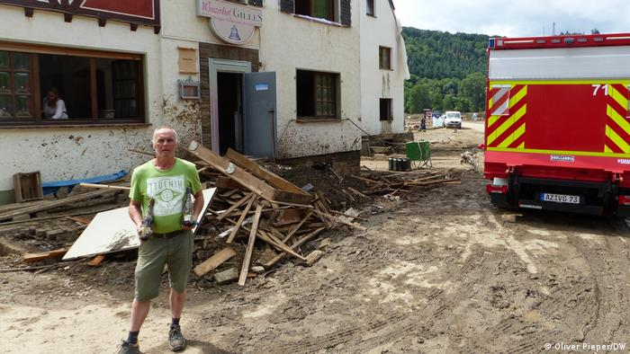 Benno Gilles surrounded by debris and mud in front of his house