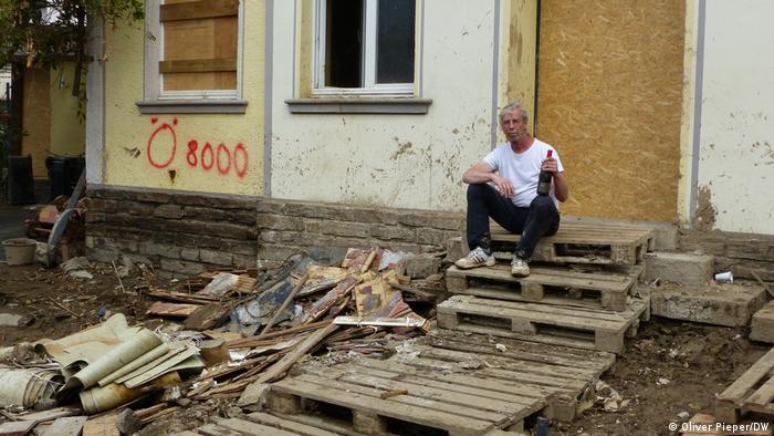 Bernd Schumacher hält seine Flasche Rotwein und sitzt auf den Stufen seines zerstörten Hauses