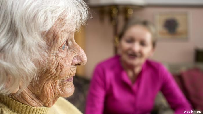 90-year-old woman with her Polish live-in caregiver in the background
