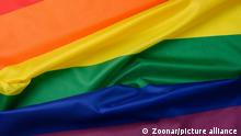 textile rainbow flag with waves, symbol of freedom of choice of lesbians, gays, bisexuals and transgender people, LGBT culture, close up