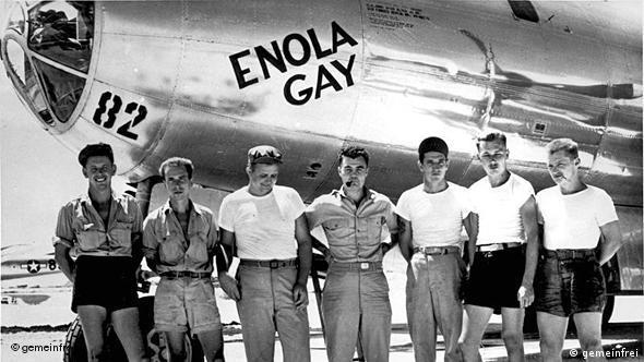 Vor dem Flugzeug mit dem Schriftzug Enola Gay stehen sieben Männer, die meisten in T-Shirts und kurzen Hosen.