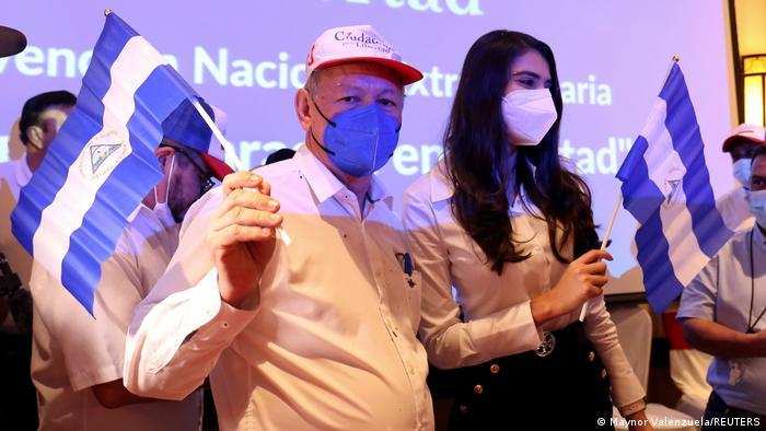 Oscar Sobalvarro and Berenice Quezada wave the Nicaraguan flag