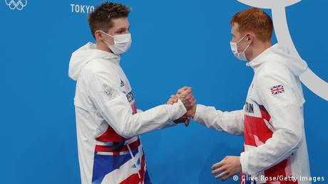 Two athletes of Team Great Britain shaking hands during a medal ceremony at the Tokyo Olympics
