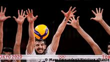Iran's Aliasghar Mojarad , center, blocks a ball during a men's volleyball preliminary round pool A match between Canada and Iran at the 2020 Summer Olympics, Wednesday, July 28, 2021, in Tokyo, Japan. (AP Photo/Manu Fernandez)
