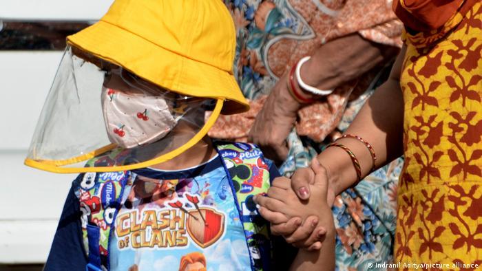 Ein Kind trägt eine Maske und Gesichtsschild