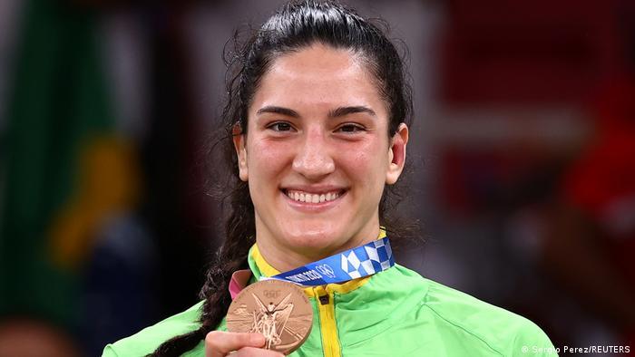 Foto mostra a judoca Mayra Aguiar sorrindo e segurando a medalha de bronze.