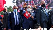 Leader of Tunisia's Islamist Ennahda party House Speaker Rached Ghannouchi waves as he holds a Tunisian flag during a rally in Tunis, Tunisia, Saturday, Feb. 27, 2021. The party, Ennahdha, led by House Speaker Rached Ghannouchi, has backed Prime Minister Hichem Mechichi in his standoff with President Kais Saied over a cabinet reshuffle. (AP Photo/Hassene Dridi)