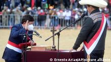 Peru's President Pedro Castillo, right, takes the oath of office of his Prime Minister Guido Bellido, during a symbolic swearing-in ceremony at the site of the 1824 Battle of Ayacucho, which sealed independence from Spain, at the Pampa de la Quinua as part of Peru´s bicentennial celebrations, in Ayacucho, Peru, Thursday, July 29, 2021, the day after he was officially sworn in as president. (AP Photo/Ernesto Arias)
